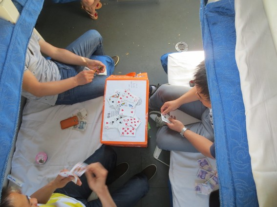 A few guys playing cards on the train to Chengdu