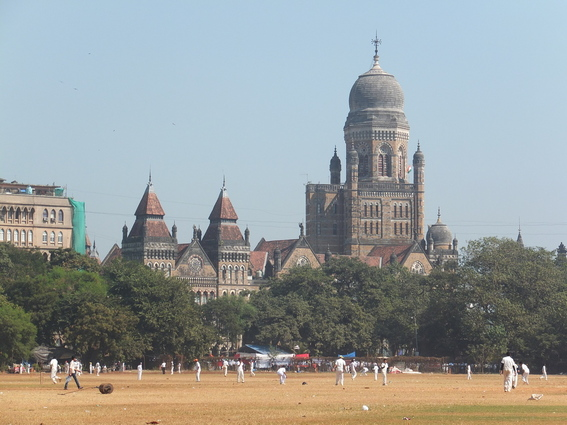 People playing cricket in the field in Mumbai