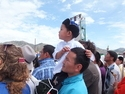 Mongolian man lifting up his son to watch the wrestling at naadam