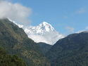 White mountain sticking up behind green mountain